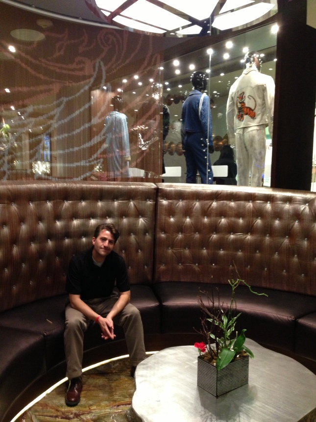Andrew hanging out in the hotel lobby near some rock star outfits.